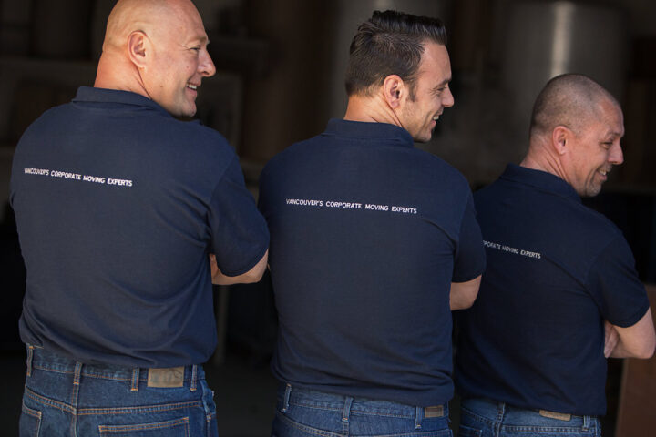 "DLO office moving experts - DLO Team showing off the back of the DLO shirts, ""Vancouvers Corporate Moving Experts"""