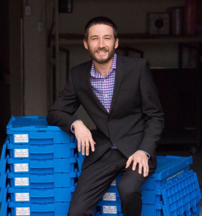DLO office moving experts - Jesse Meyer sitting on blue bins