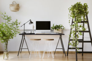 DLO office moving experts - Computer desktop on desk with lamp in white freelancer's interior with plants and stools. Real photo