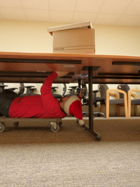 Chris Whitten with santa hat under the table